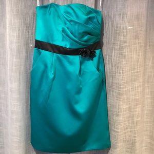 Green cocktail dress w/ black flower embellishment